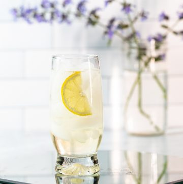 Light yellow cocktail with a lemon wedge in front of a vase filled with purple flowers.