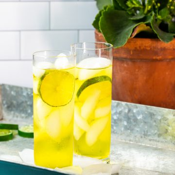 Two bright yellow cocktails on a metal tray.