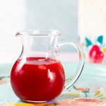 Small pouring pitcher with bright red syrup inside.