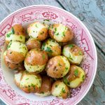 Red and white bowl filled with parsley covered potatoes.