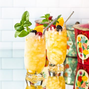 Two bright yellow cocktails garnished with fruit, mint and a metal straw.
