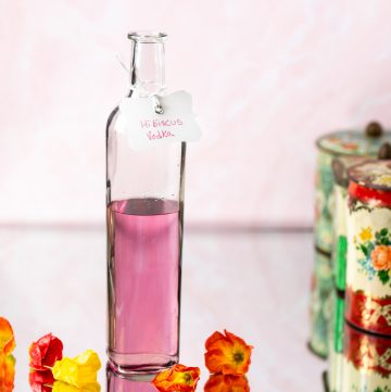 Bottle filled with pink liquid and labeled hibiscus vodka.
