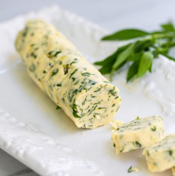White plate with herb butter sliced on it.