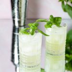 Two pale green cocktails garnished with basil.