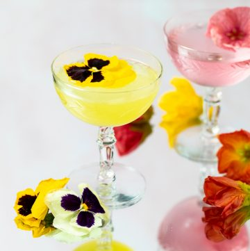 Bright yellow cocktail garnished with a pansy flower.