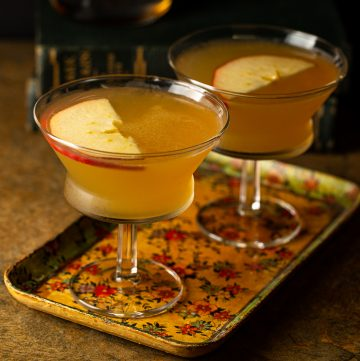 Two apple brandy sidecars on a vintage tray.
