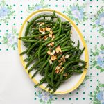 Platter of green beans with toasted almonds on top.