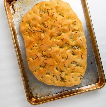 Focaccia bread on a cookie sheet.