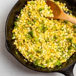Cast iron skillet with corn and green peppers.