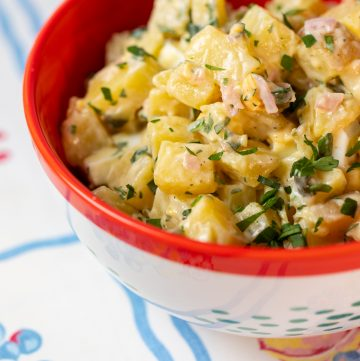 Red bowl filled with potato salad.