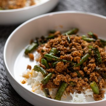 White bowl with ground pork and green beans.